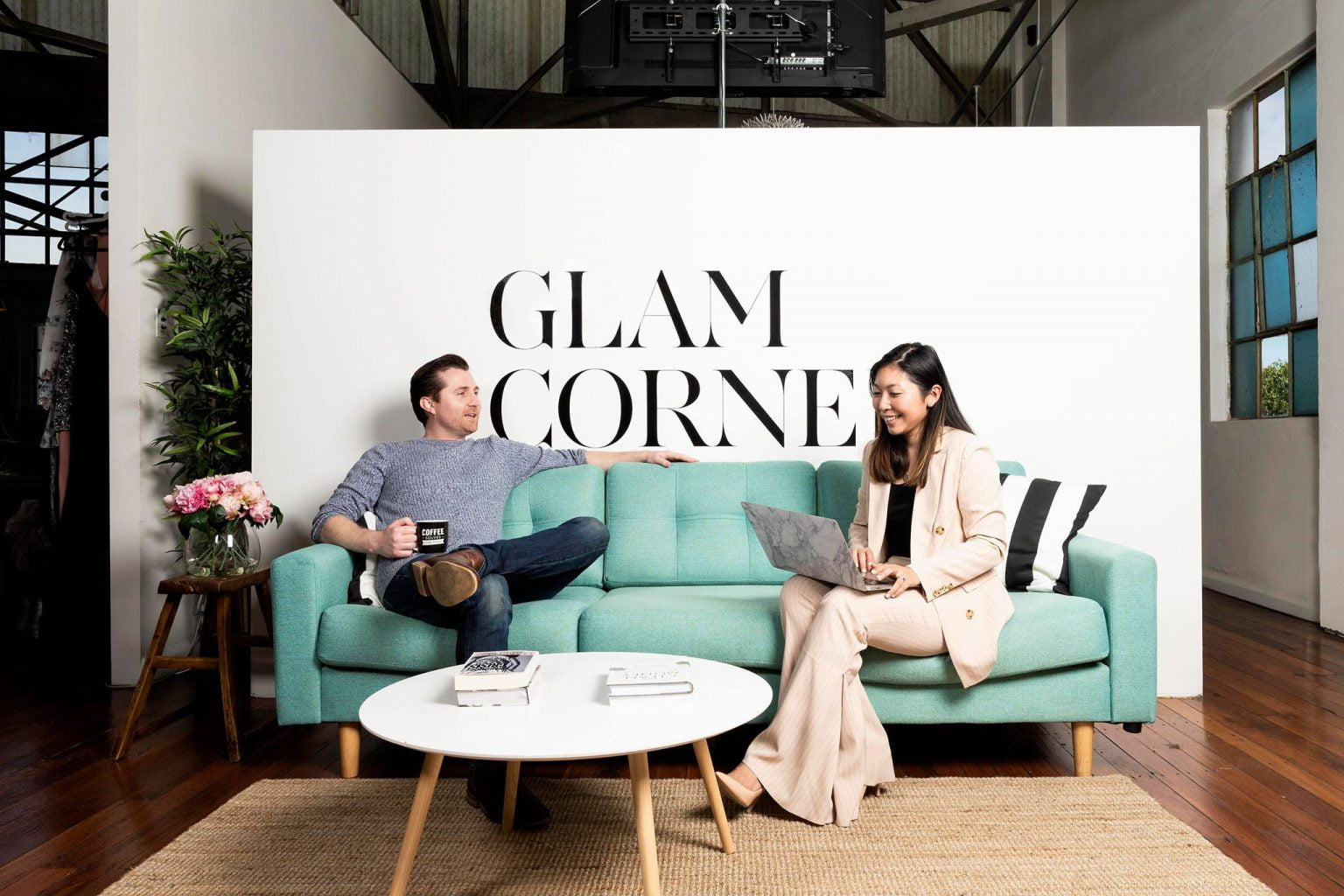 Co-founders of GlamCorner, Dean and Audrey Jones. Behind them, a large banner with the logo for GlamCorner is shown.